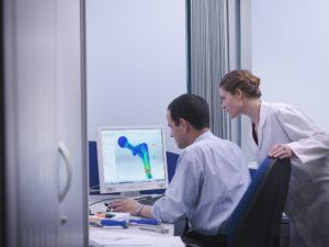 a man and a woman looking at a computer screen with CAD design